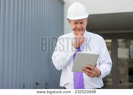Focused Man In Formalwear And Helmet Looking At Tablet Screen Outdoors. Construction Expert Reviewin