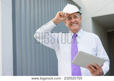 Happy Senior Man In Formalwear And Helmet Holding Tablet And Looking At Construction Site. Property