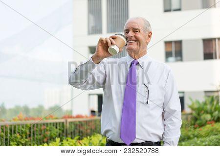 Happy Senior Man In White Shirt And Tie Drinking Takeaway Coffee In Office Park. Businessman Enjoyin