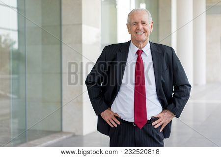 Portrait Of Happy Senior Man In Suit And Tie Standing At Modern Business Center. Smiling Businessman