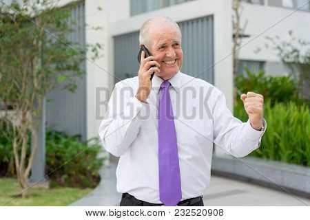 Happy Senior Man In Formalwear Talking On Mobile Phone And Making Winning Gesture Outdoors. Business
