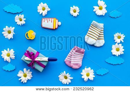 Pregnancy And Preparation For Childbirth. Pregnancy Test Near Flowers On Blue Background Top View.