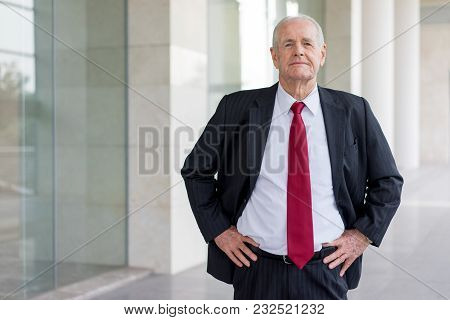 Portrait Serious Senior Man In Suit And Tie Standing Near To Modern Office Building. Pensive Busines