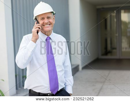 Smiling Senior Man In Tie And Helmet Talking On Phone At Construction Site. Chief Architect Reportin