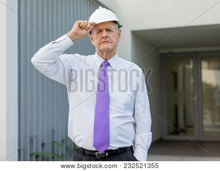 Portrait Of Serious Strict Man In Tie And Helmet Outdoors. Building Owner Inspecting Construction Si