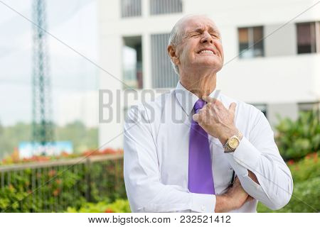 Upset Senior Man In Formalwear With Suffering Grimace Trying To Loosen Tie Outdoors. Exhausted Busin