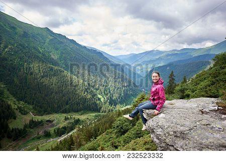 Happy Beautiful Woman Tourist Sitting On Rock Edge, Looking To The Camera, Enjoying Breathtaking Vie