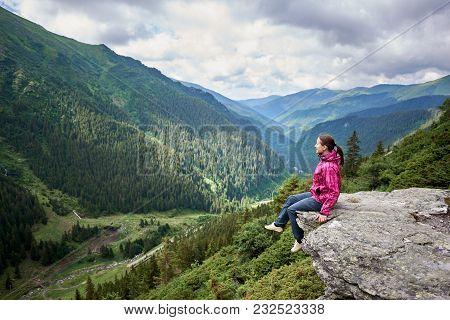 Smiling Beautiful Female Tourist Sitting On Rock Edge Admiring Breathtaking View Of Green Grassy Slo