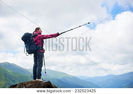 Full Length Of A Female Backpacker Pointing Away With Her Trekking Pole Copyspace Direction Navigati