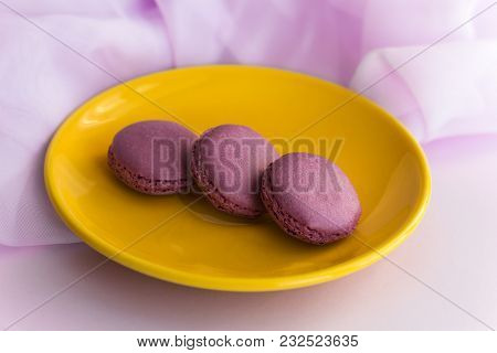 Three Macaroons On A Yellow Plate On The Table