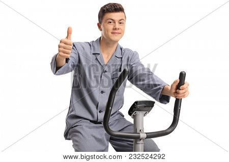 Teenager in pajamas on an exercise bike making a thumb up sign isolated on white background