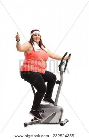 Overweight woman exercising on a stationary bike and making a thumb up gesture isolated on white background