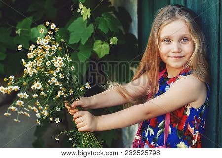 Portrait Of A Little Girl With Daisies . Adorable Baby Holds In His Hands The Flowers Of The Field