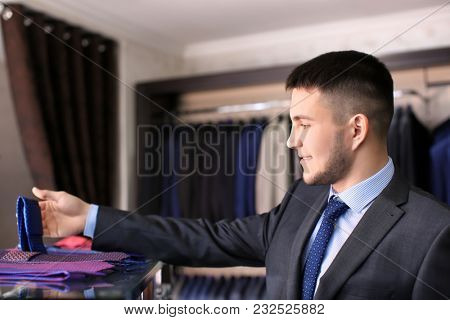 Man choosing necktie to match his suit in boutique