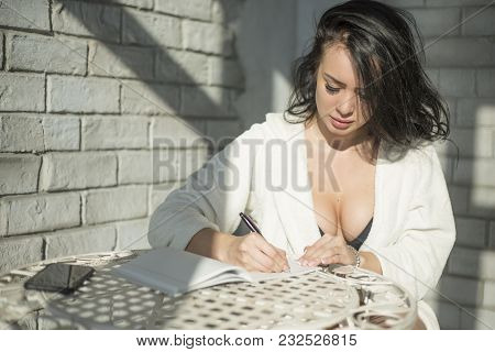 Busy Morning. Attractive Young Woman Writing Something Down While Sitting On The Summer Terrace.