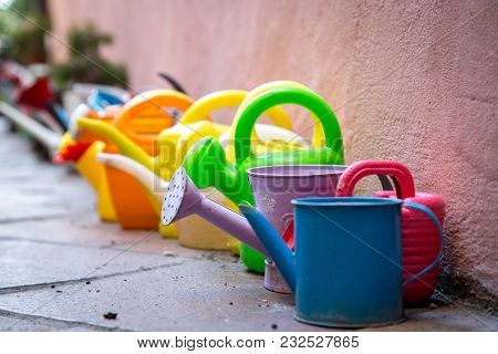 A Row Of Colorful Watering Cans For Decoratiojn