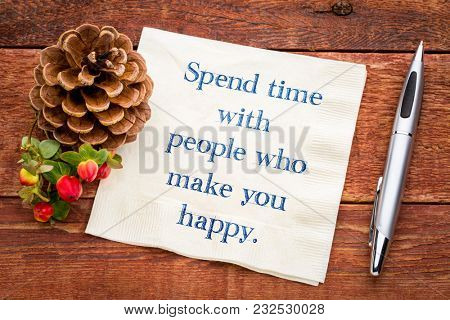 Spend time with people who make you happy. Handwriting on a napkin with a cup of tea