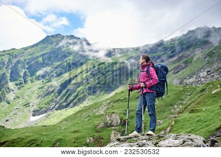 Woman Backpacker Resting While Hiking Standing On Top Of A Rock Enjoying Fantastic Mountain Scenery