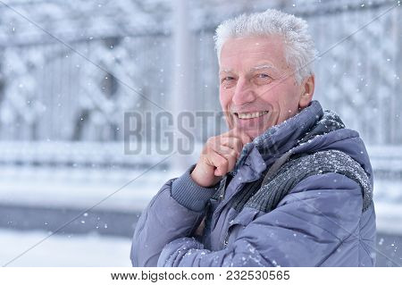 Portrait Of Smiling Senior Man Standing Outdoors In Winter