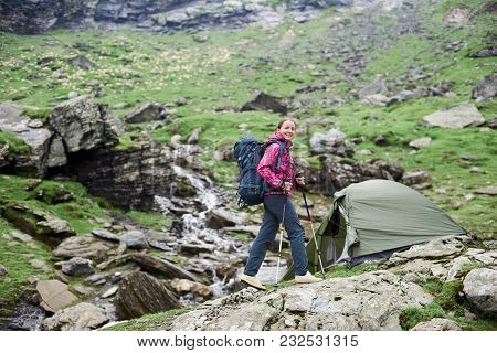 Happy Woman Hiker Smiling To The Camera Walking With Her Backpack In The Mountains Valley Copyspace