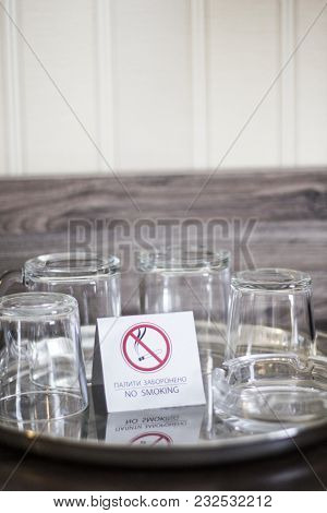 Glass Cups With A Plate No Smoking. Glasses In The Ukrainian Hotel. No Smoking. Glasses On A Tray