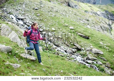 Overcoming Obstacles. Young Female Climber Walking Down Grassy Rocky Hill In Green Beautiful Mountai
