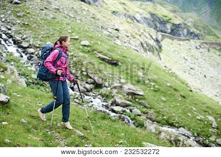 Happy Young Woman Hiking In The Mountains With Her Backpack And Trekking Poles Copyspace Exploring N