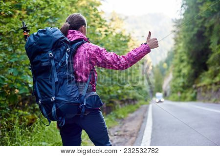 Low Angle Rear View Shot Of A Female Hiker With A Backpack Hailing Calling Catching A Car On Bicaz C