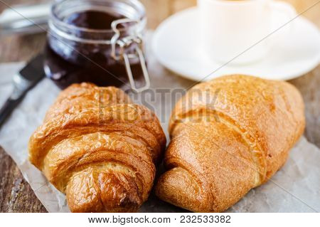 Two Croissants And A Cup Of Coffee On A Wooden Table