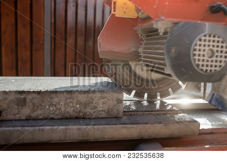 An Angle Grinder Or Circular Saw With A Concrete Block