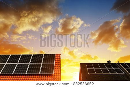 Solar energy panel on the roof of the house in the background sunset sky. The concept of ecological housing.