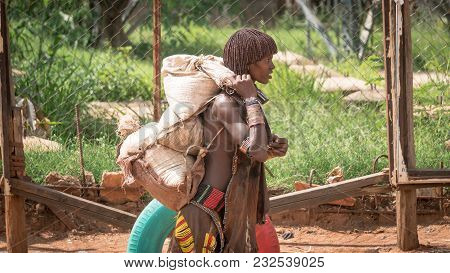 Omo Valley, Ethiopia - September 2017: Unidentified Woman From The Tribe Of Hamar Carrying Goods In