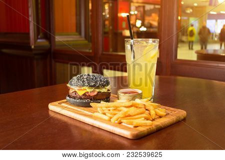 Black Burger French Fries And A Cup With Tomato Sauce On A Wooden Board, With A Glass Of Lemonade A
