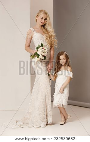 The Female Bride And Little Pretty Girl With Flowers Dressed In Wedding Dresses. Lovely Little Girlf