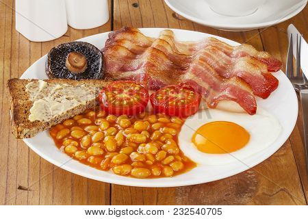 Full English Breakfast On An Old Pine Kitchen Table.