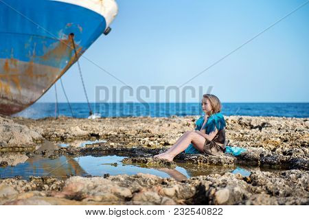 Cute Beautiful Girl Sits On Rocky Stones On The Sea Shore Ocean And Looks Dreamily With A Large Aban