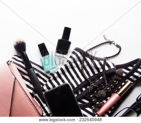 Stylized feminine flatlay with glasses, foundation, lip gloss, powder, brush, handbag, striped shirt isolated on white top view. Woman accessories from above copy space for text. poster