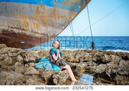 Attractive Sweet Young Girl Child Sitting On A Sea Rocky Shore Near An Abandoned Ship
