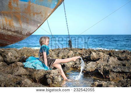 Cute Girl Sits On A Rocky Seashore And Joyfully Splashes With Her Feet In The Water Against The Back