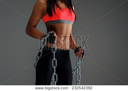 Body Of Fitness Woman In Sportswear Holding Chain. Isolated On Grey Background