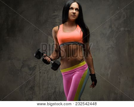 Sporty Woman With Long Black Hair In A Colorful Sportswear Holding One Dumbbell.