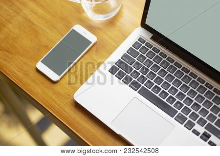 Laptop, Smart Phone & Glass Of Water On Coffee Shop Table