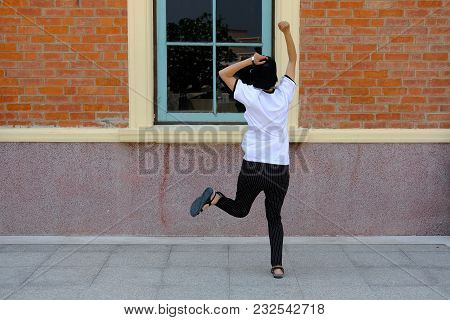 Backside Of Woman Jumping With Gladness Outdoors.