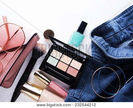 Top view of woman jeans shirt, concealer pallet, lip gloss, nail polish, bracelet, powder brush on white background.