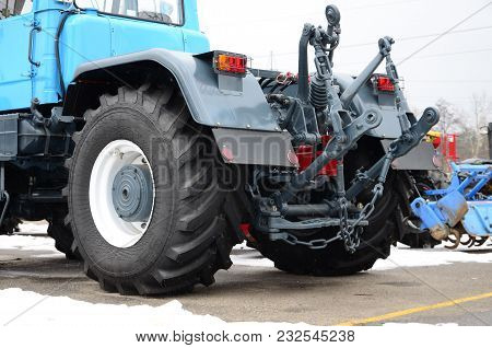 Wheels Of Back View Of New Tractor In Snowy Weather. Agricultural Vehicle Back View