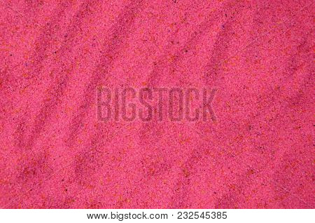 Texture Of A Colored Granular Sand Close Up. Pink Grains