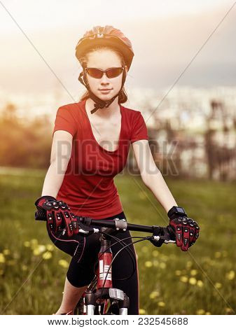 Woman traveling bicycle in summer park. Womens road bike for running on green grass aganist blue sky with white clouds. Cycling trip is good for health. Female in school trip. School trip.