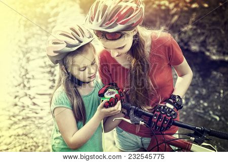 Bikes cycling weekend for girls. Children training rides bicycle in cycling look at compass. People lost their way traveling unaccompanied. Toning photo of school trip. Effect of film.