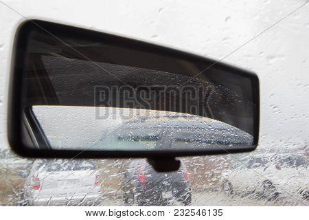 Drops Of Rain On Glass Background. Street Bokeh Lights Out Of Focus. Inside Car When Rainning