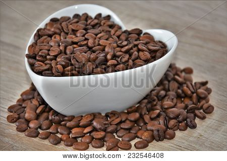 Grains Of Coffee In A White Cup And Scattered On A Wooden Table
